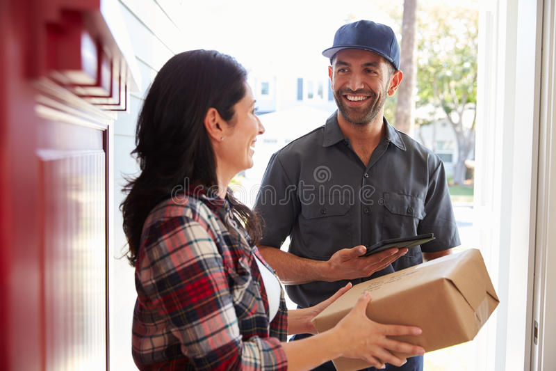 Woman Receiving Package From Courier At Home royalty free stock photo