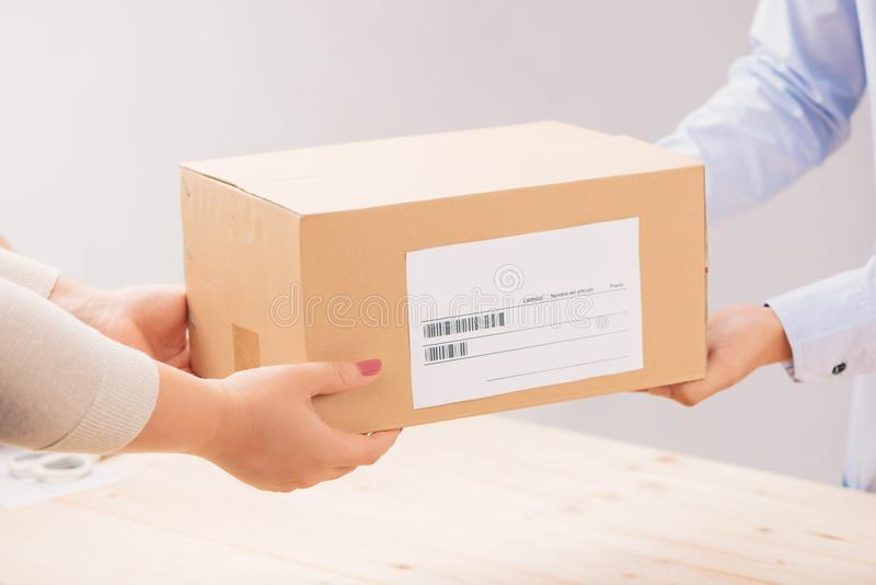 Woman receiving package from a delivery man.  royalty free stock photos