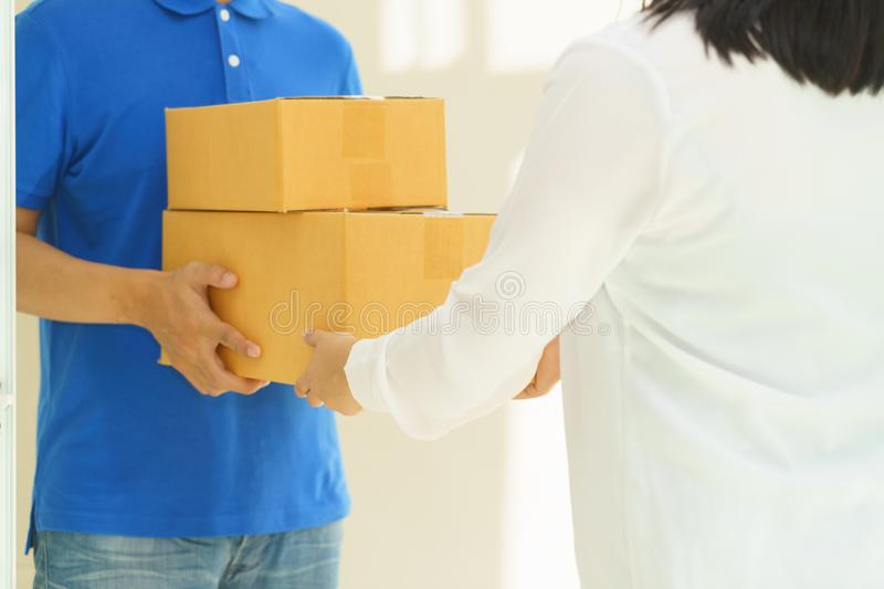 Woman receiving package from delivery man.  stock photos
