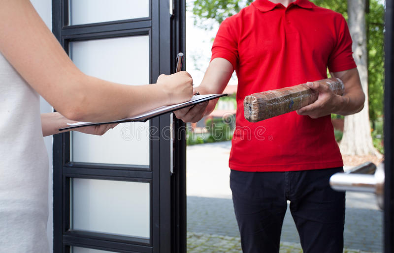 Woman receiving a package from delivery man royalty free stock photos