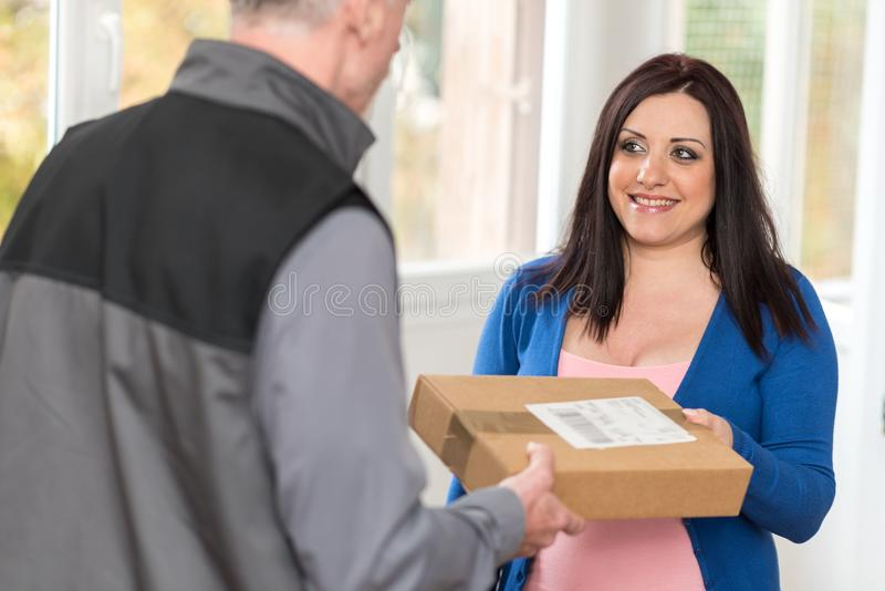 Woman receiving package from delivery man. Pretty woman receiving package from delivery man stock photography