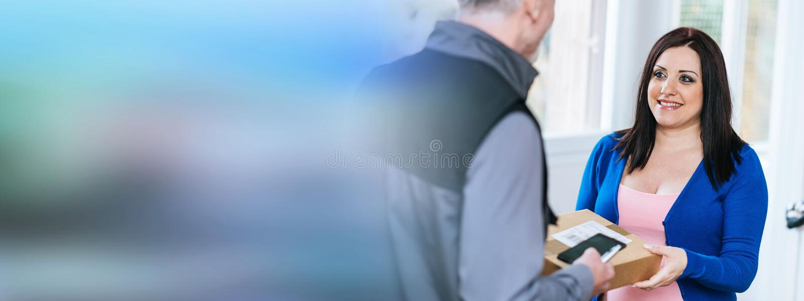 Woman receiving package from delivery man. Pretty women receiving package from delivery man stock photo