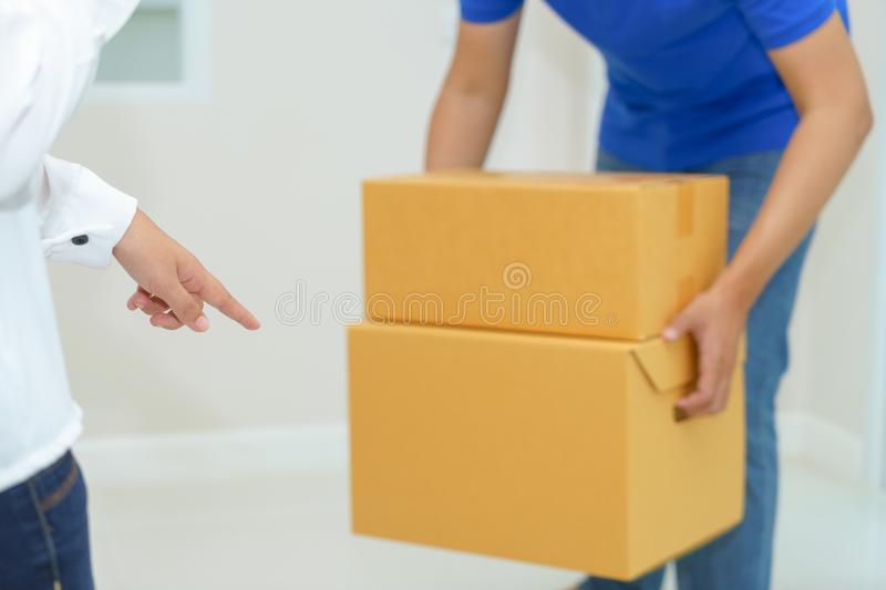 Woman receiving package from delivery man - put it down. Woman receiving package from delivery man stock photography