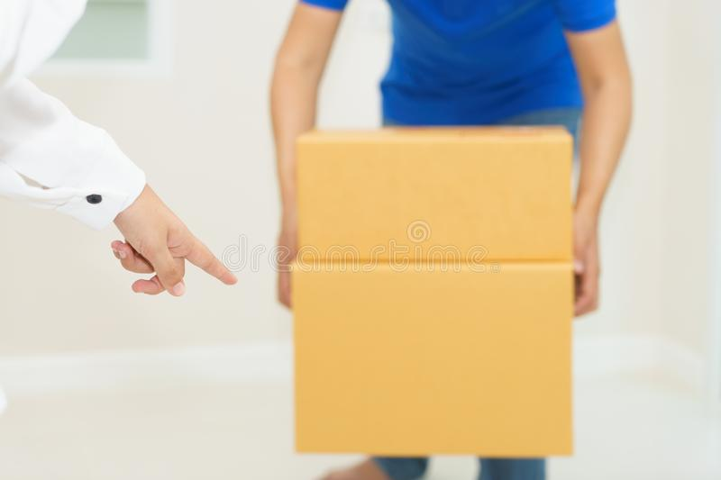 Woman receiving package from delivery man - put it down. Woman receiving package from delivery man - put it down royalty free stock image