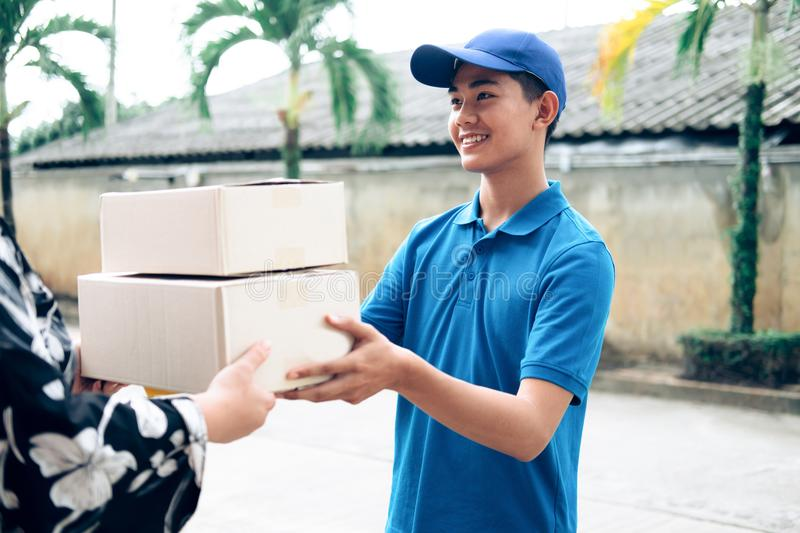 Woman receiving package from delivery man. Delivery, mail, people and shipping concept royalty free stock photos