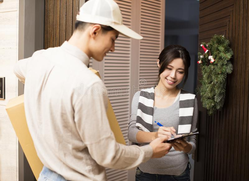 Woman receiving package from delivery man. Young women receiving package from delivery man royalty free stock photography