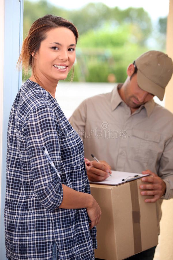 Woman receiving package. At her front door royalty free stock image