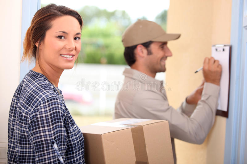 Woman receiving a package. From the mailman royalty free stock photo