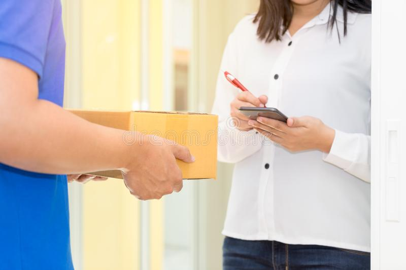 Woman receiving package and signing on digital mobile phone from stock images