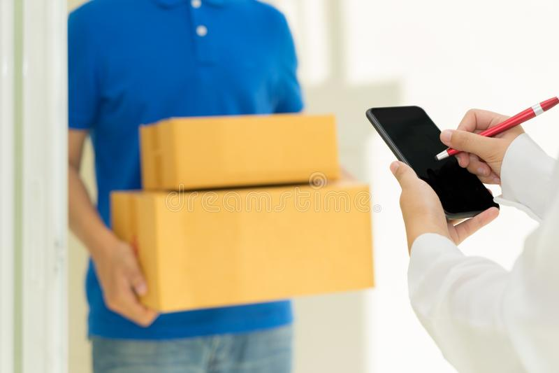 Woman receiving package and signing on digital mobile phone from. Delivery man stock image