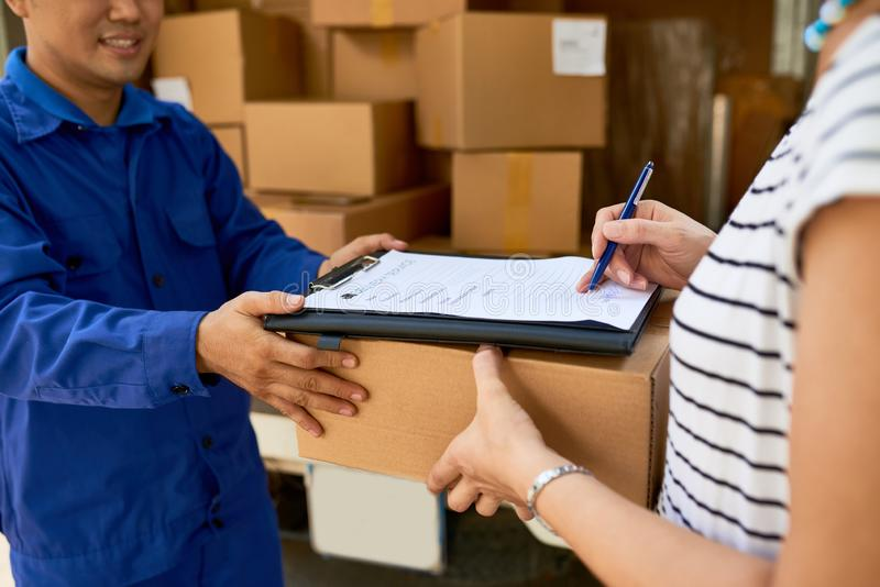 Woman receiving package. Woman signing document when receiving her package stock image