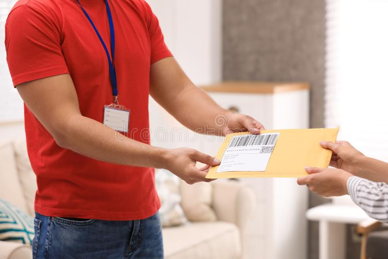 Woman receiving padded envelope from courier at home. Closeup royalty free stock photo