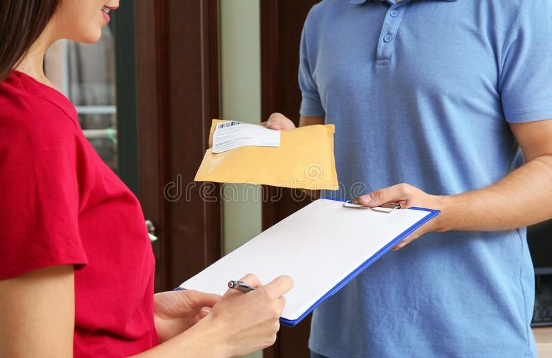 Woman receiving padded envelope from delivery service courier indoors. Closeup royalty free stock image