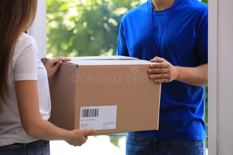 Woman receiving parcel from courier on doorstep. Closeup stock images