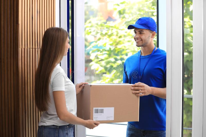 Woman receiving parcel from courier. On doorstep royalty free stock image