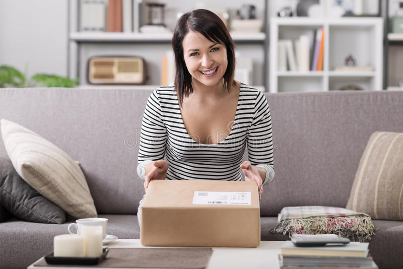 Woman receiving a parcel. Smiling young woman at home on the couch, she has received a postal parcel, online shopping and delivery concept royalty free stock photography