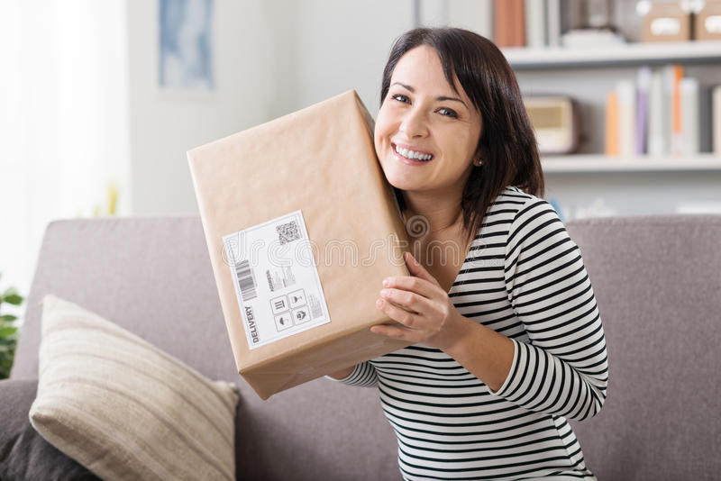 Woman receiving a parcel. Smiling young woman at home on the couch, she has received a postal parcel, online shopping and delivery concept royalty free stock image