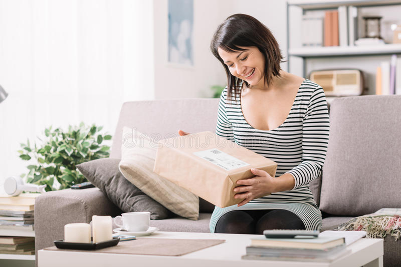 Woman receiving a parcel. Smiling young woman at home on the couch, she has received a postal parcel, online shopping and delivery concept royalty free stock photos