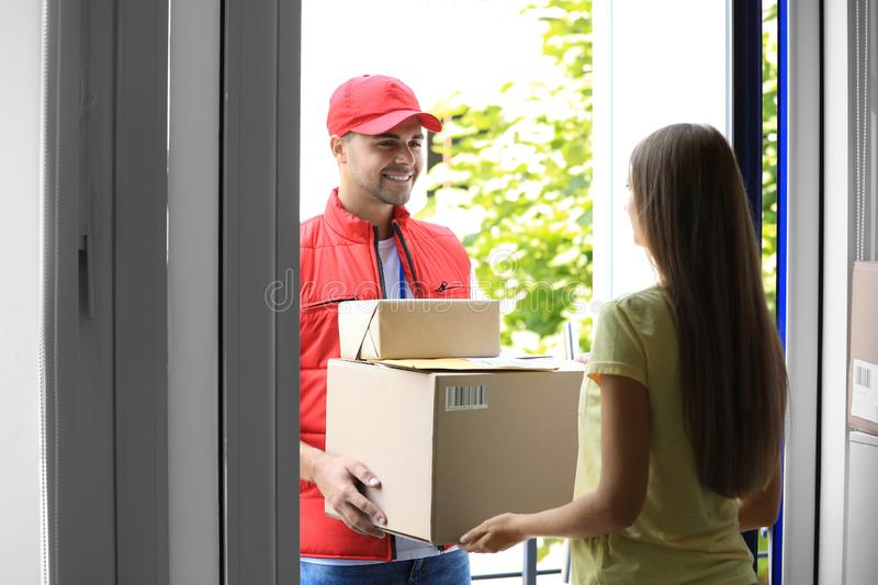 Woman receiving parcels from courier. On doorstep royalty free stock photo
