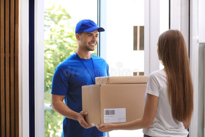 Woman receiving parcels from courier. On doorstep stock photography