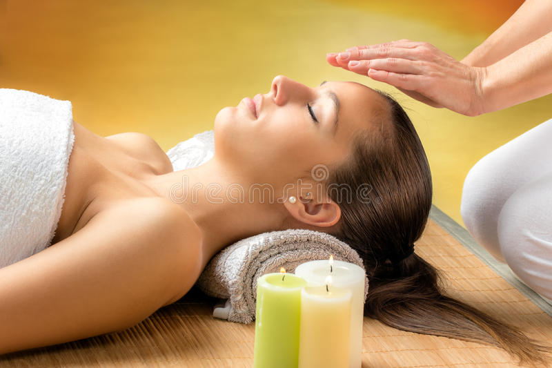 Woman receiving reiki treatment on forehead. stock photography
