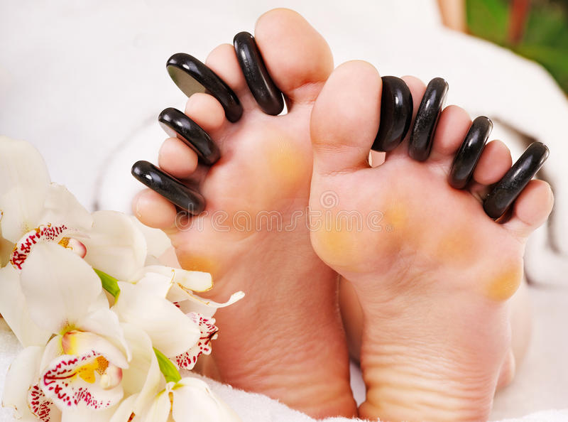 Woman receiving stone massage on feet. stock photo
