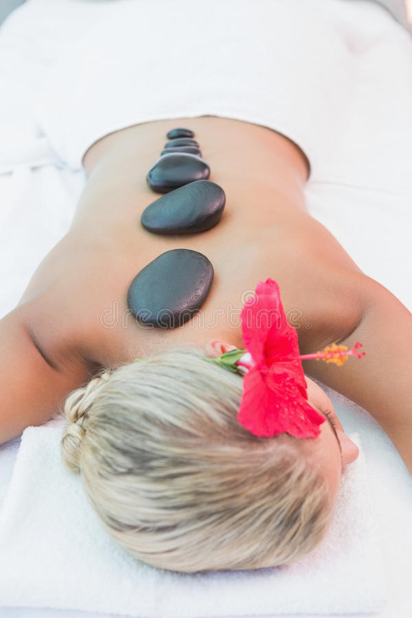 Woman receiving stone massage at health farm. Close-up of a beautiful young woman receiving stone massage at health farm royalty free stock images