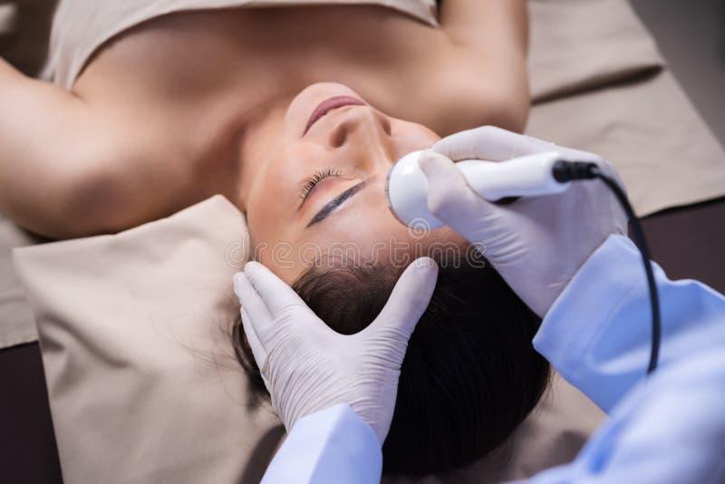 Woman receiving ultrasound facial beauty treatment skin care stock photo