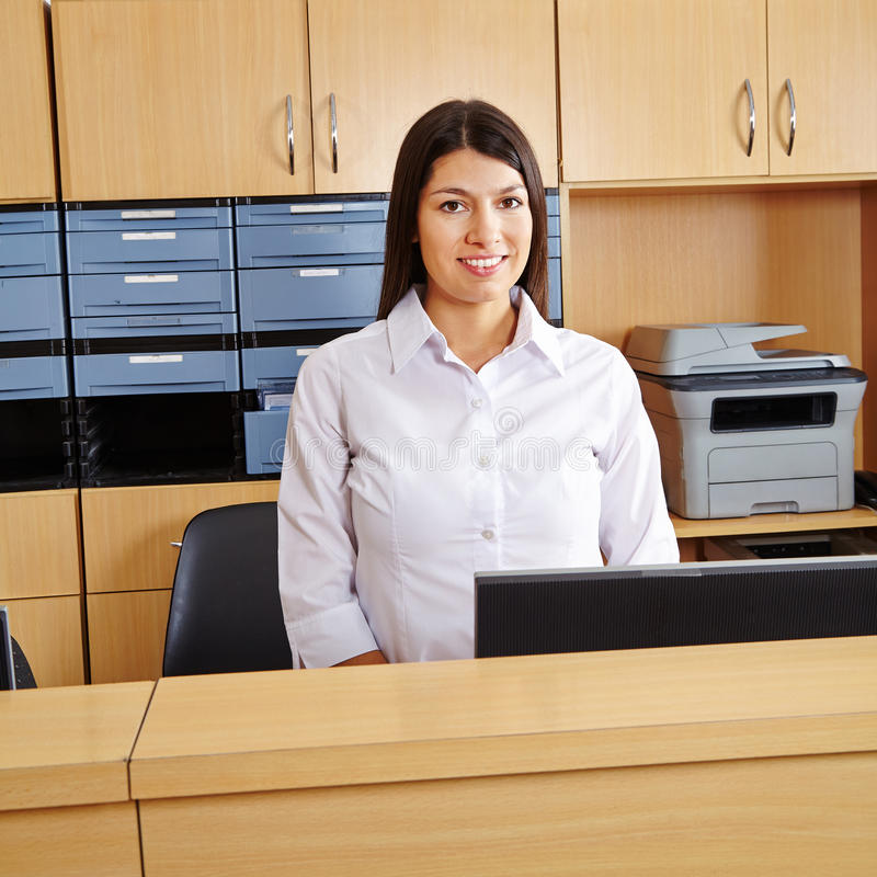 Woman at reception in hospital. Smiling happy woman workingt at reception in a hospital stock image