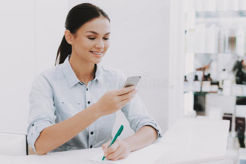 Woman Receptionist Looks at Phone in Beauty Salon. Woman Receptionist. Reception Workplace. Workplace in Beauty Salon. White Interior. White Reception Desk stock photo