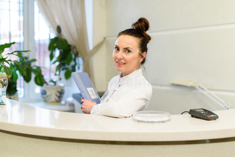 Woman receptionist in medical coat stands at reception desk stock photos