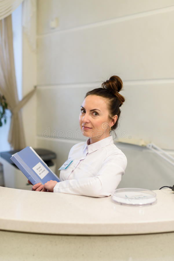 Woman receptionist in medical coat stands at reception desk royalty free stock images