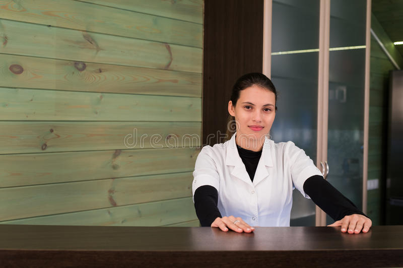 Woman on receptrion smiles and welcomes the virtual visitor at spa or modern clinic. Papers with agreement in your hand. Woman on receptrion smiles and welcomes royalty free stock image