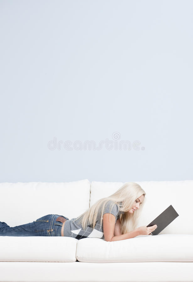 Download Woman Reclining On Couch With Book Stock Photo - Image: 12824668