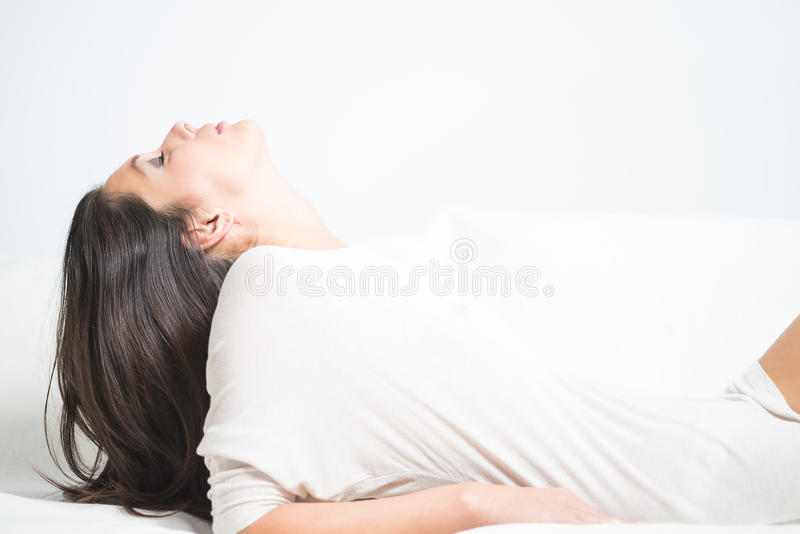 Woman reclining with her head tilted back stock photo