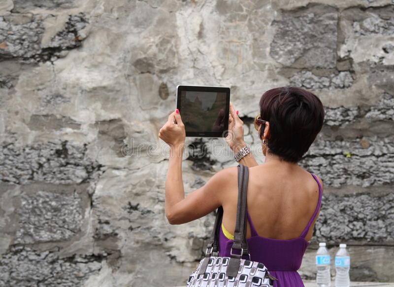 Woman Recording Festival with Tablet. OTTAWA, CANADA – AUGUST 5: A woman using a Samsung tablet to record the Chateau Laurier Hotel and Rideau Canal royalty free stock photo