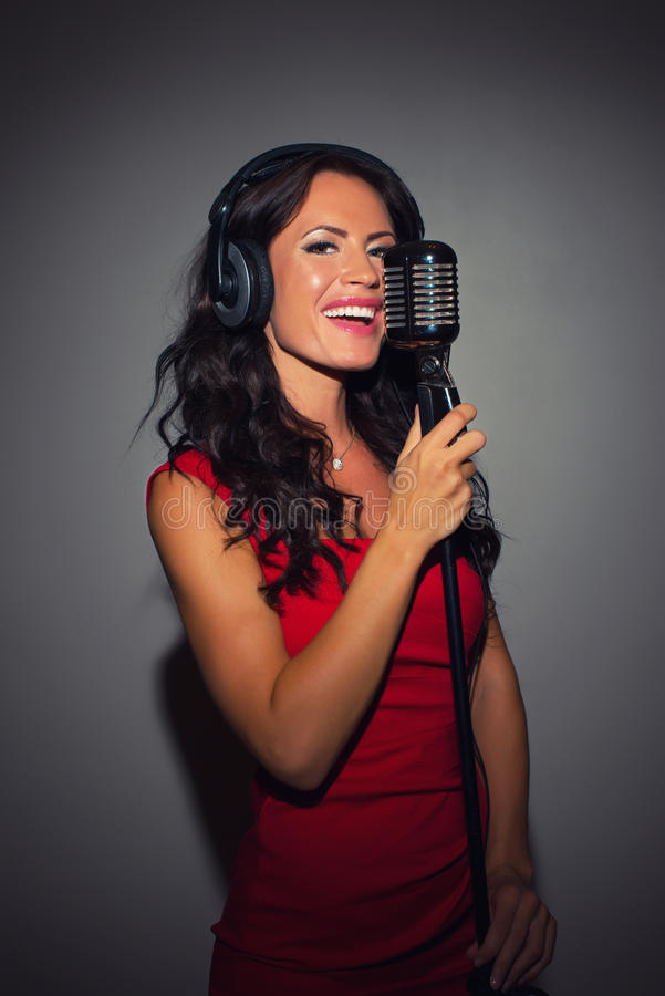 Woman recording a song. Attractive brunette woman recording a song in music studio stock photos
