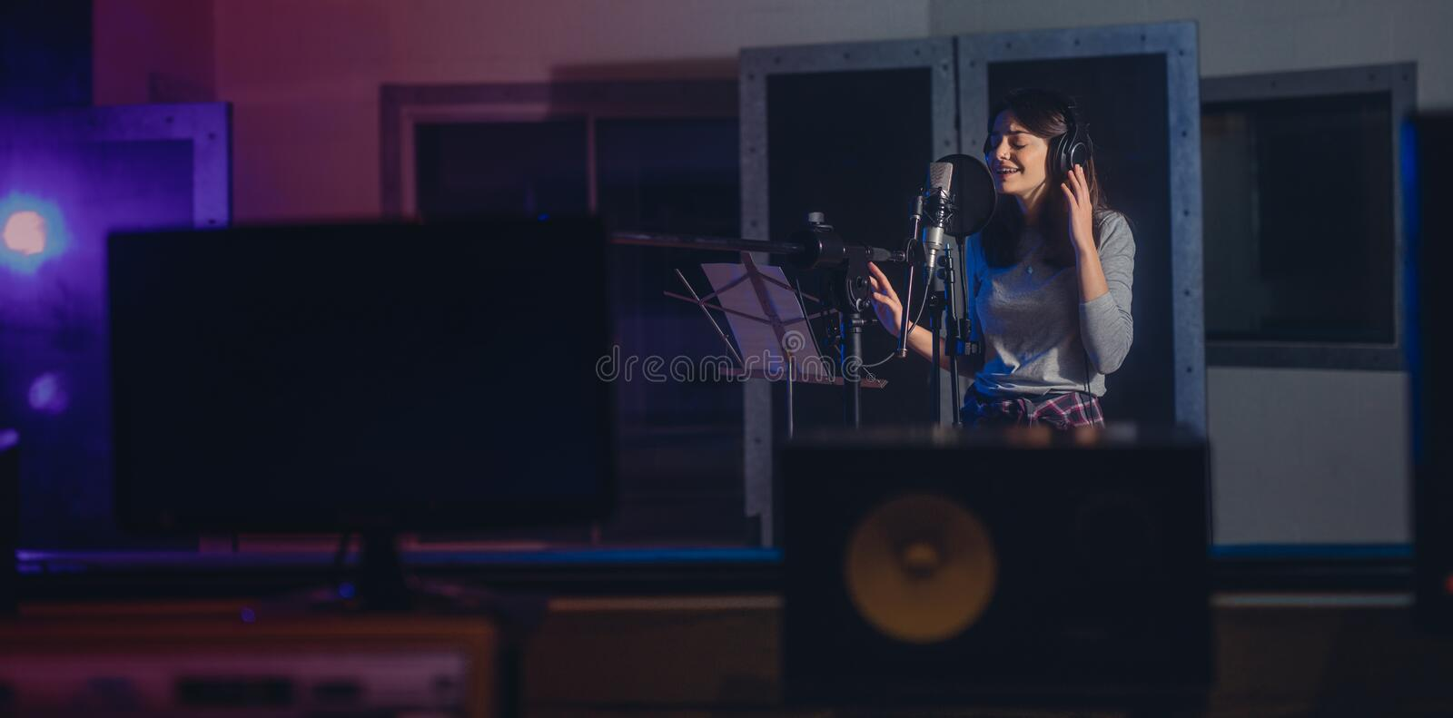 Woman recording a song in music studio. Female playback singer recording her album stock image