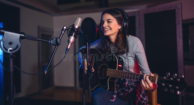 Woman recording a song in a professional music studio stock image