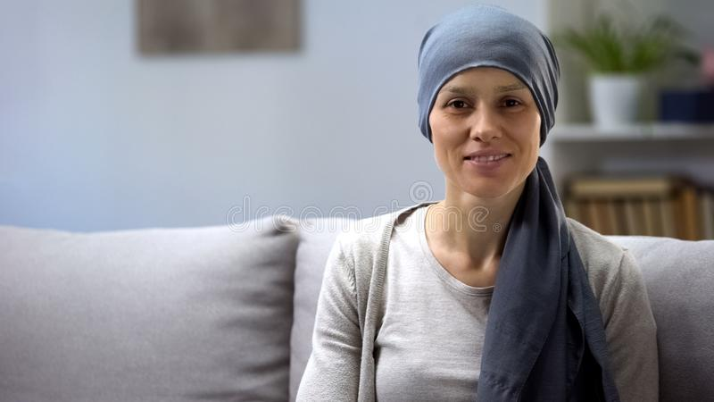 Woman recovering after chemotherapy looking at camera, survivor, background stock images