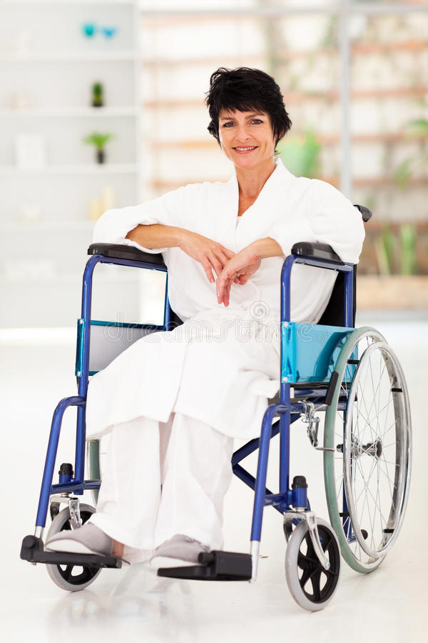 Woman recovering injury. Middle aged woman sitting on wheelchair recovering from injury stock photography