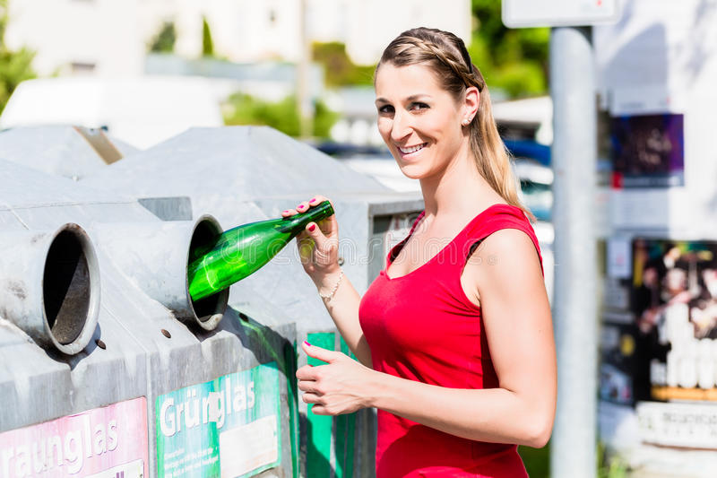 Woman on recycling center throwing bottles in container stock images