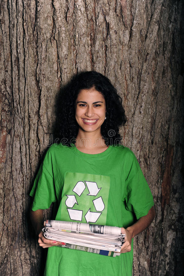 Woman with recycling sign holding newspapers. Woman with recycling sign on shirt holding newspapers in front of tree royalty free stock photo