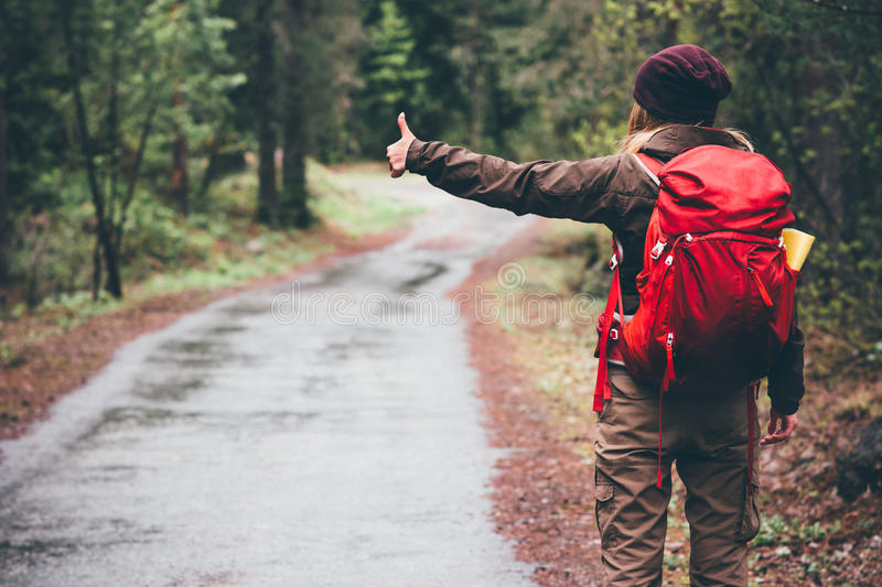 Woman with red backpack hitchhiking alone. On the road Travel Lifestyle concept rear view stock image