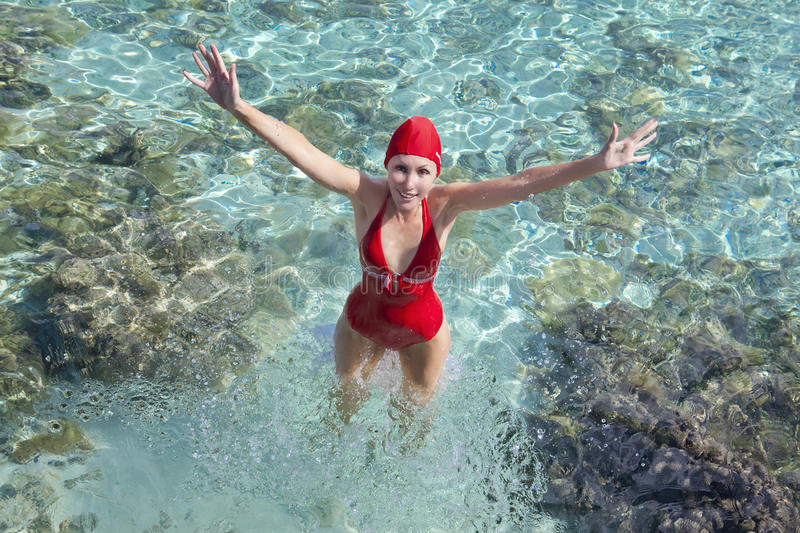 Woman in a red bathing suit standing in the sea and gives to us hands royalty free stock image