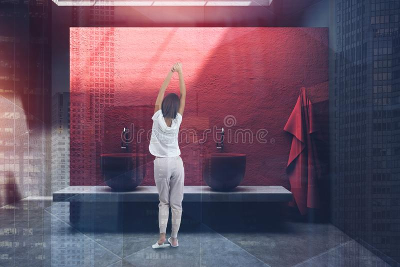 Woman in red bathroom with double sink stock image