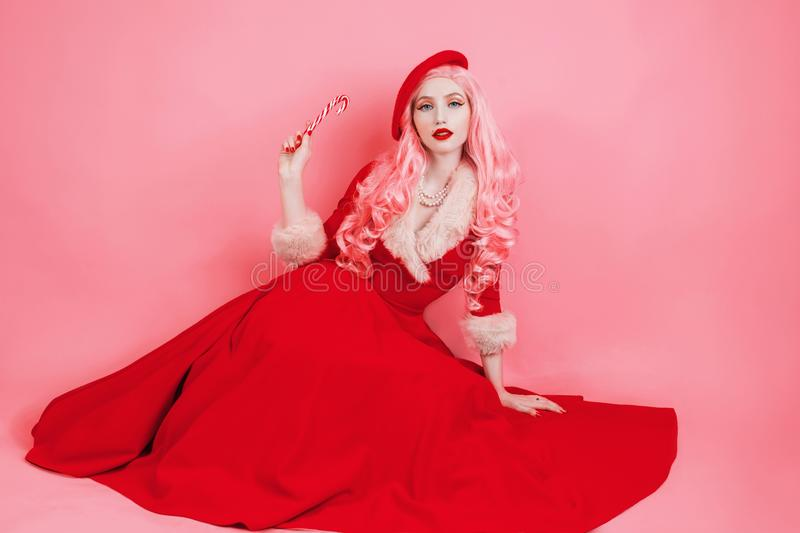 Woman in red christmas dress in hat on pink background. Sexy santa girl hold lollipop. New year concept. Beautiful model with long. Hair. Celebrate New Year stock photography