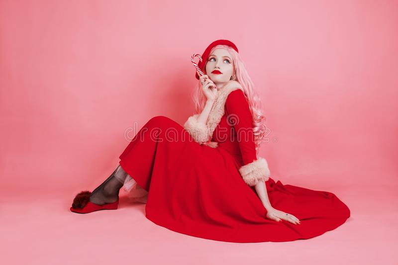 Woman in red christmas dress in hat on pink background. Sexy santa girl hold lollipop. New year concept. Beautiful model with long stock image