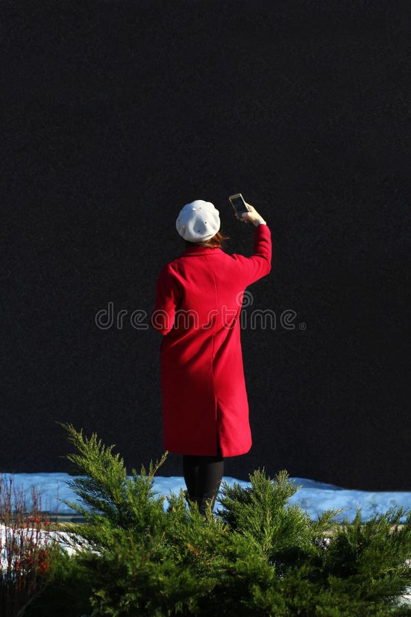Woman in red coat making selfie on a sunny day. Back view stock photo