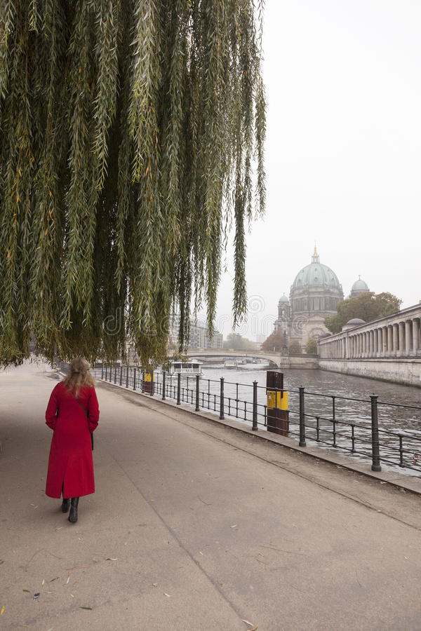 Woman in red coat under weeping willow near river spree in berlin. Woman in red coat under weeping willow near river spree and berliner dom in berlin stock photography